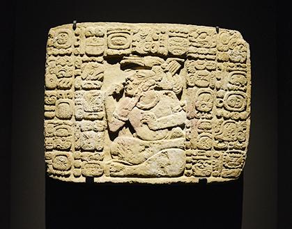 A Tonina, cette plaque a été mise sur la tombe du fondateur de la dynastie lors d'une cérémonie organisée par le 8e roi (31 octobre 799). Les glyphes précisent la date de l'événement et le nom du 8e roi ainsi qu'un de ses faits d'armes. Dix ans auparavant (13 juillet 789), il avait fait prisonnier un noble ennemi qui figure au centre dans une posture craintive. Une longue bande de papier à son oreille indique son sacrifice imminent.