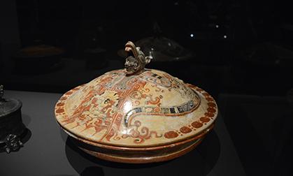 Sur le couvercle de ce plat qui se trouve dans la salle des rites funéraires, on peut voir un iguane de sa gueule sortent plusieurs têtes humaines.