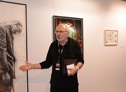 """Philippe Piguet, commissaire de l'exposition : """"le dessin engagé"""" devant un homme qui vit dans la rue d'Ernest Pignon-Ernest."""