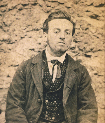 Jean-François Troppmann photographié à Mazas en costume de ville le 9 octobre 1869 par Jules Verrier. Il a été installé devant un des murs en meulière. Il est logé au rez-de-chaussée dans une cellule double 4-6 afin que le gardien puisse être avec lui en permanence. Son procès débutera le 26 décembre. Il sera guillotiné le 19 janvier 1870.