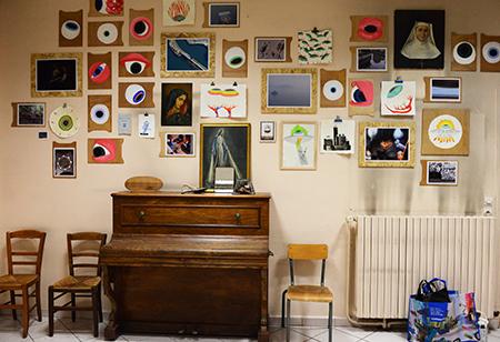 La pièce réunit des objets trouvés sur place dans les locaux, chaise, tableaux, piano...